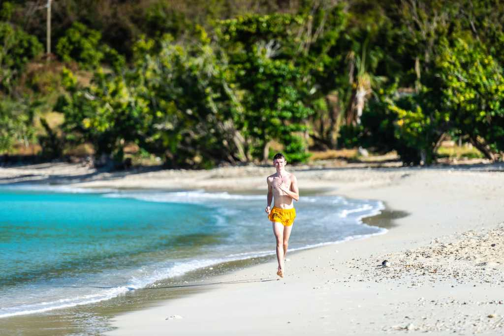 Young man running on shore at Brewers Beach on St. Thomas USVI