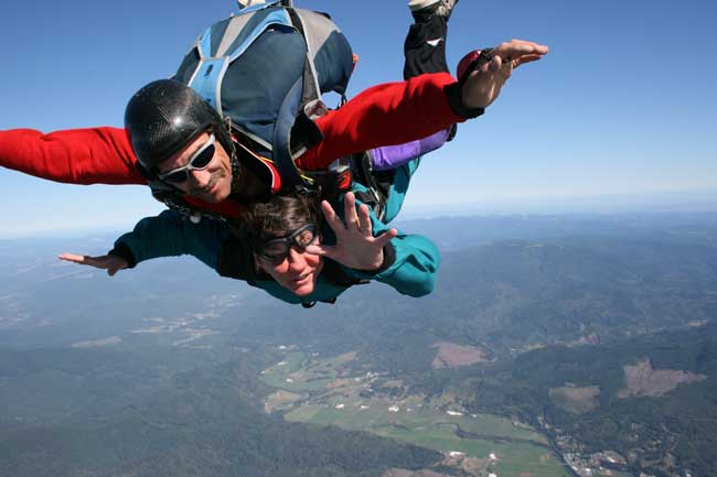 Image of Rick and Darian's skydive, Darian is waving at the camera.
