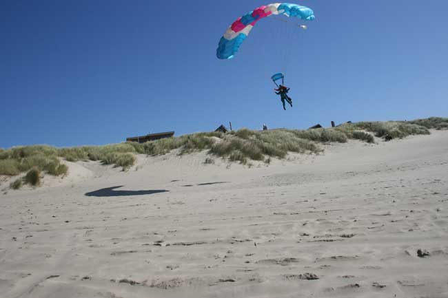 Image of Rick and Darian skydiving, they are just about to land on a beach