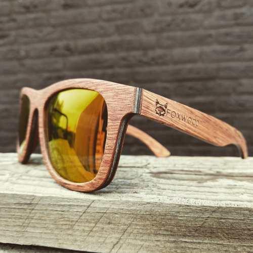 Foto van houten foxwood zonnebril op een houten plank tegen een achtergrond van zwarte bakstenen