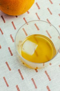 Blood and Sand cocktail with pyramid ice cube against a fabric background with an orange in the top right corner - The Mummy
