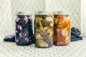 three pickling jars with different color contents against a fabric background - The Mummy