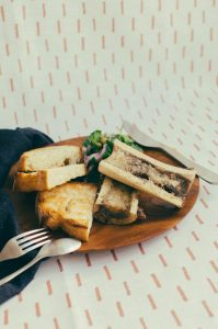 Vertical shot of plate with 2 pieces of bone marrow, 3 pieces of toast and salad against a fabric background - The Mummy