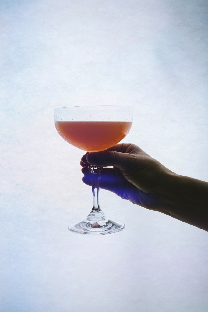 Image of silhouetted hand holding an orange cocktail for our menu pairing with Punch-Drunk Love