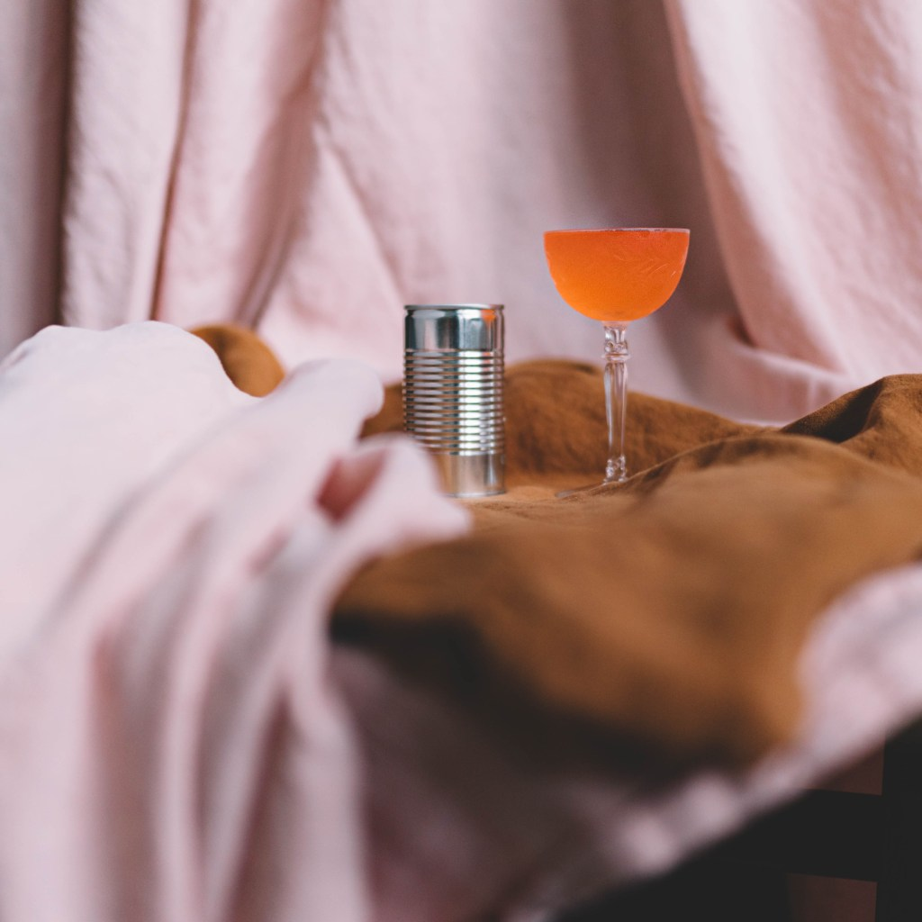 A cocktail named Light and Day sits next to a single tin can of juice. There is rust and blush-colored cloth partially obscuring the view of the two. The blush cloth is draped in the background. This was a consistent setting for our 10 Cloverfield Lane post.
