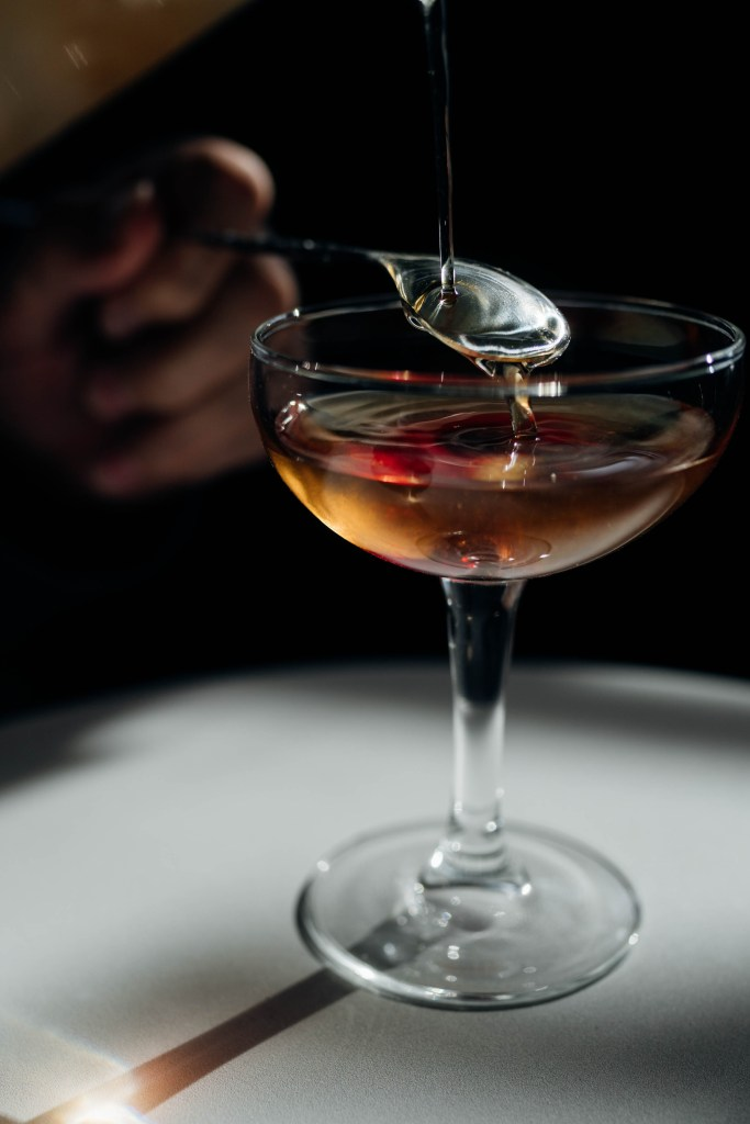 Close up of a bar spoon where you can see the ripples of the cocktail being poured on to it, cascading into the coupe glass below. To the left you can see a hand out of focus holding the bar spoon.