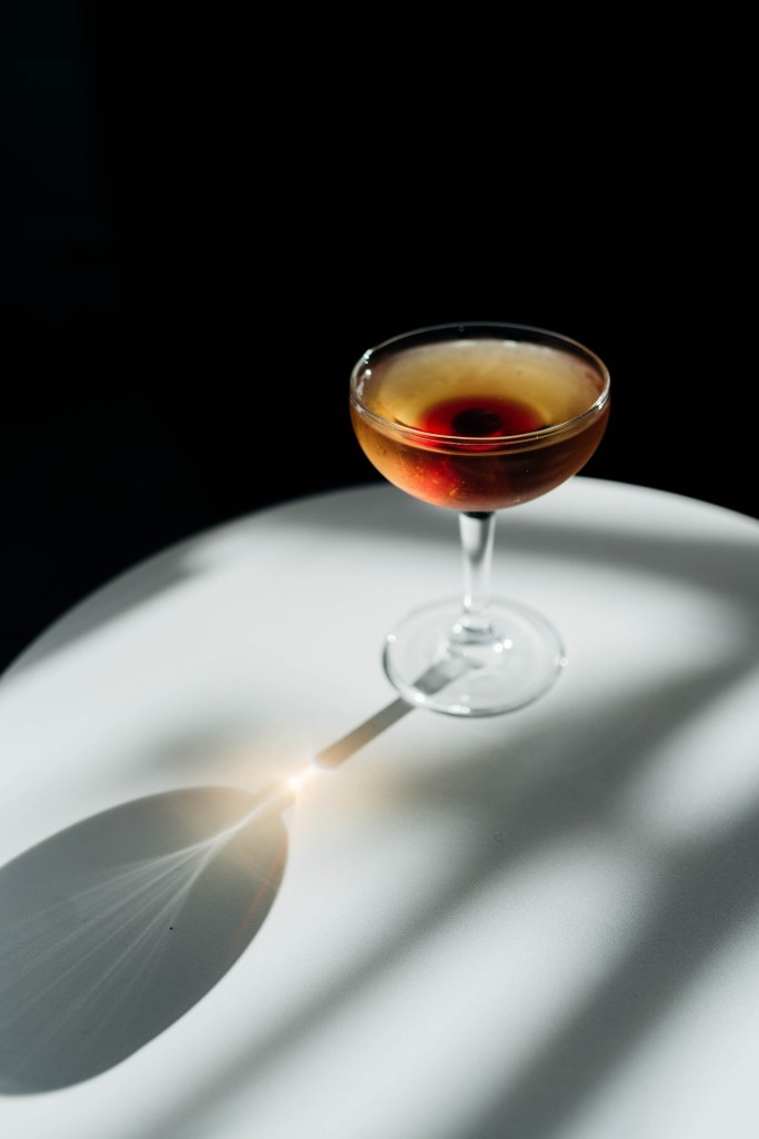 For our Home Alone post we made a Thumbprint Cookie Cocktail that features a light brown liquor in a coupe glass and cherry and its juices sitting in the bottom of the glass. The glass is standing on a white round table against a black backdrop.