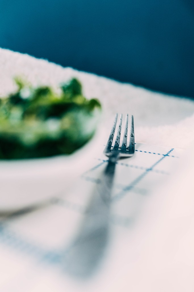 With an extremely shallow field of view you can see dew droplets on the tines of a fork sitting next to the Leafy Herb Salad that is out of focus on the left-hand side of the frame. A white and blue backdrop sits around the fork tines.