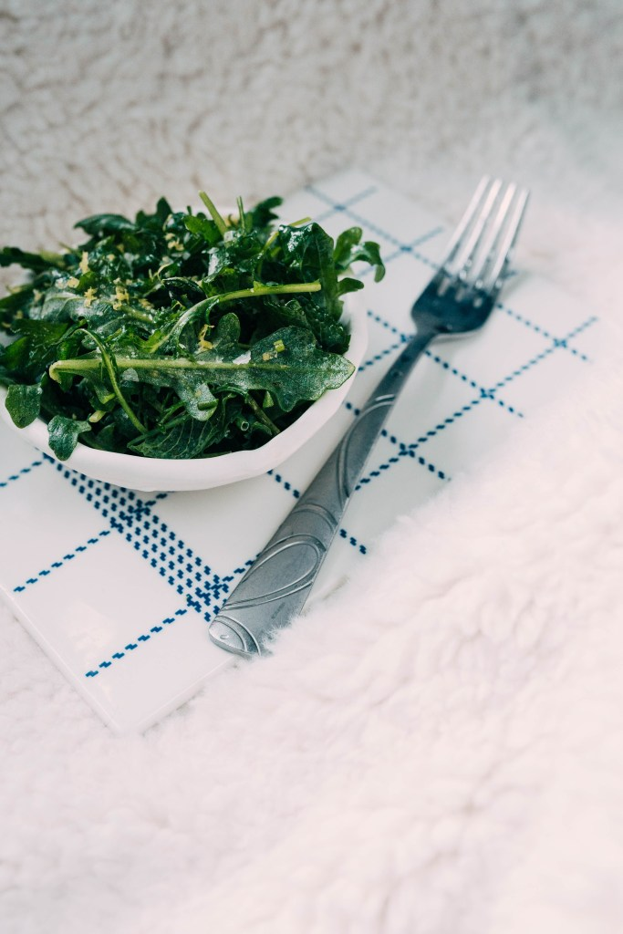 Surrounded by a white blanket sits a frozen Leafy Herb Salad in a bowl. Bits of salt and Lemon zest can be see on top of the leafy greens. The bowl is above a white and blue grid-like plate with a fork on right-hand side of the salad.