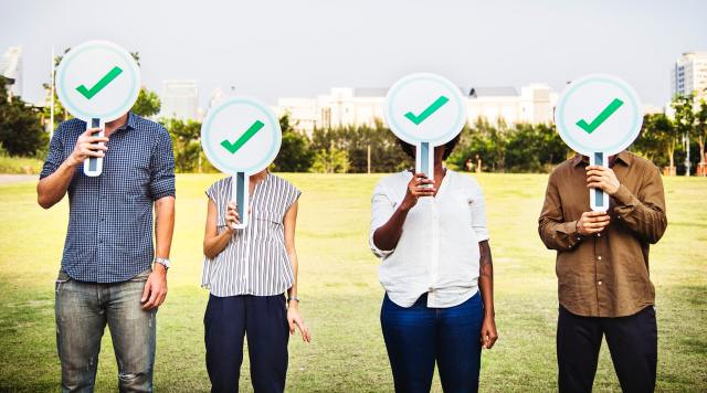 four people in the yard with green checklist sign