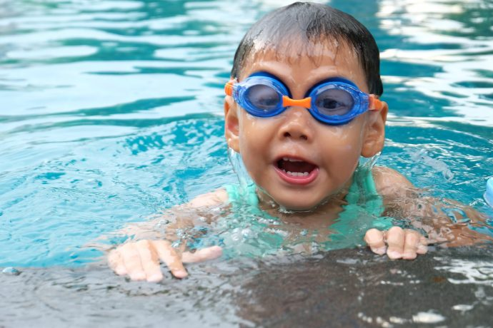 child with goggles in pool