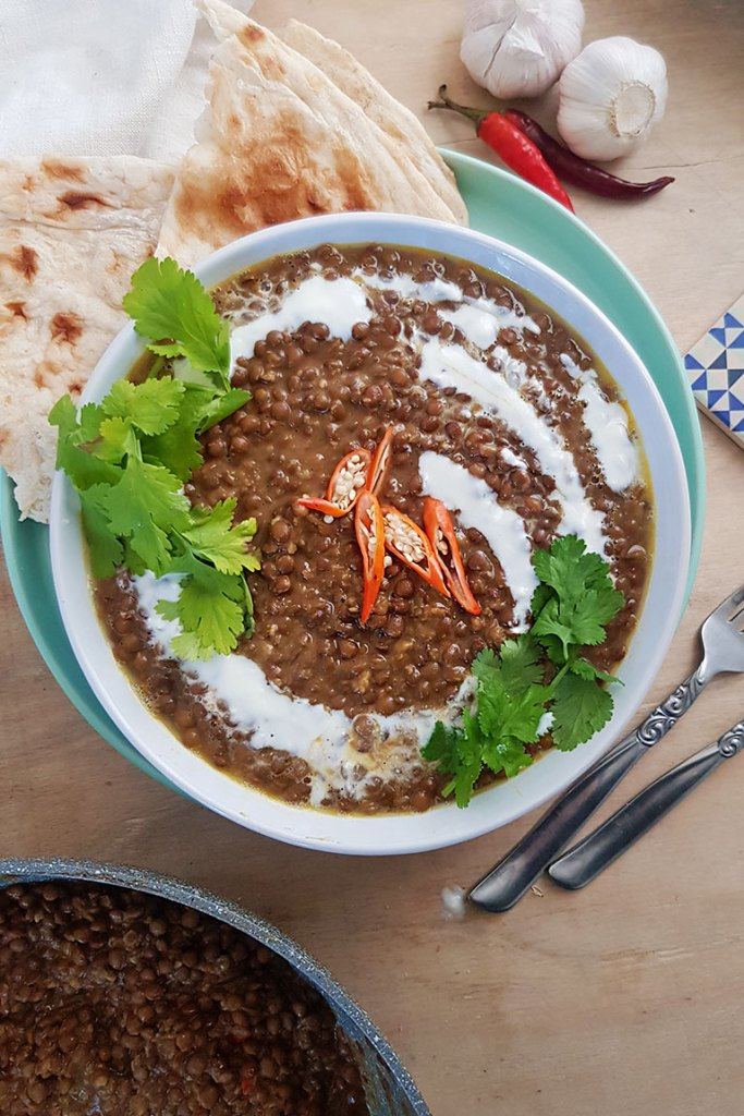 Lentil curry served in white bowl, garnished with coconut cream and fresh coriander leaves.