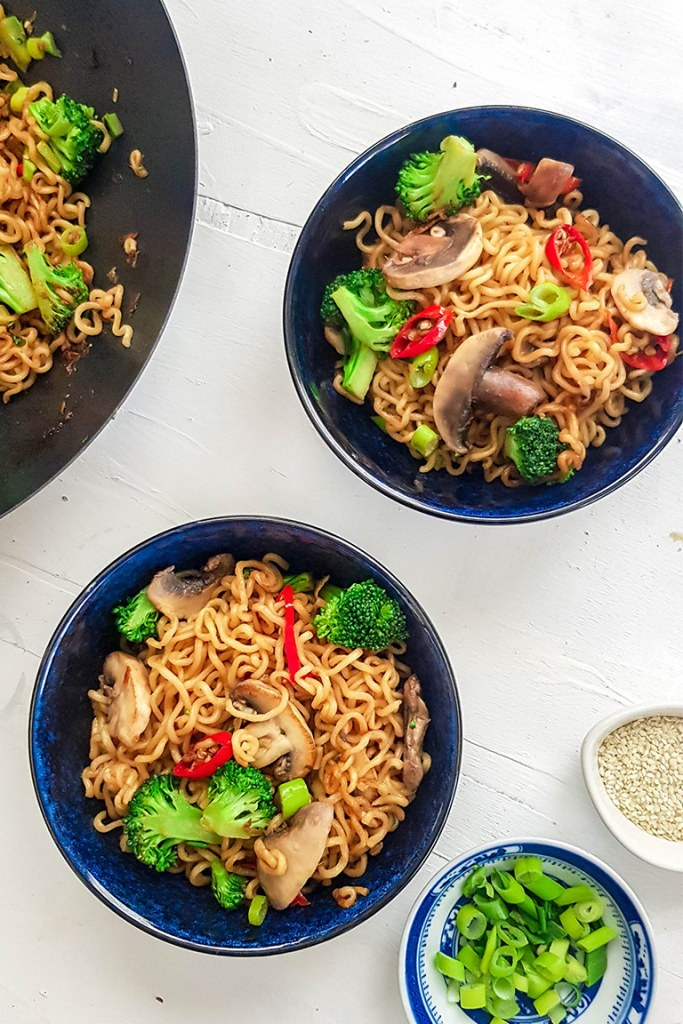 ramen stirfry served in two bowls and a wok
