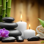 zen scene w bamboo, black rocks, purple orchid, white candles and a folded white towel