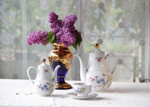 Tea in a cup, a bouquet of a lilac and beautiful service for Nancy Knows Us