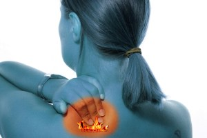 head and shoulder view of woman rubbing her back with orange spot indicating back pain