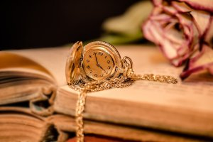 soft toned image of a book, a watch, and a rose