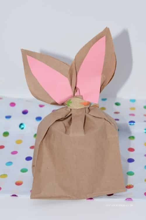 Create the easter bunny paper treat bags by adding the pink construction paper and ribbon to complete it.