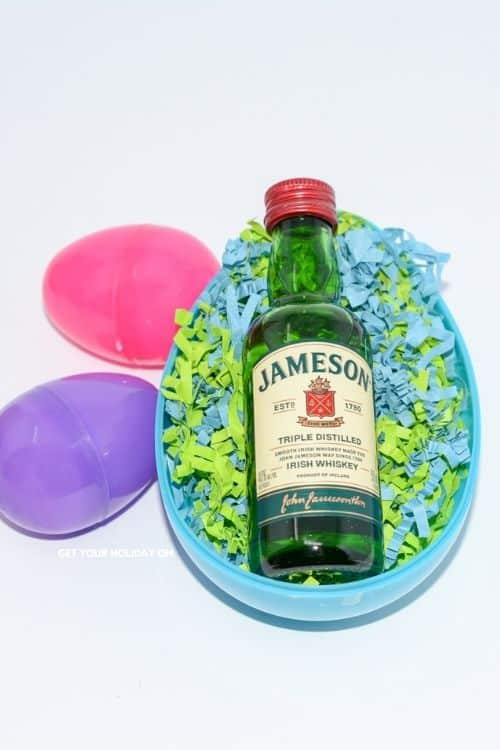 A large blue Easter egg with a mini bottle of Jameson with crinkled blue and green paper for filling for the best booze Easter egg hunt.