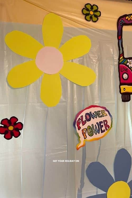 flowers made out of poster board and placed on the diy tablecloth for a tie dye feel.