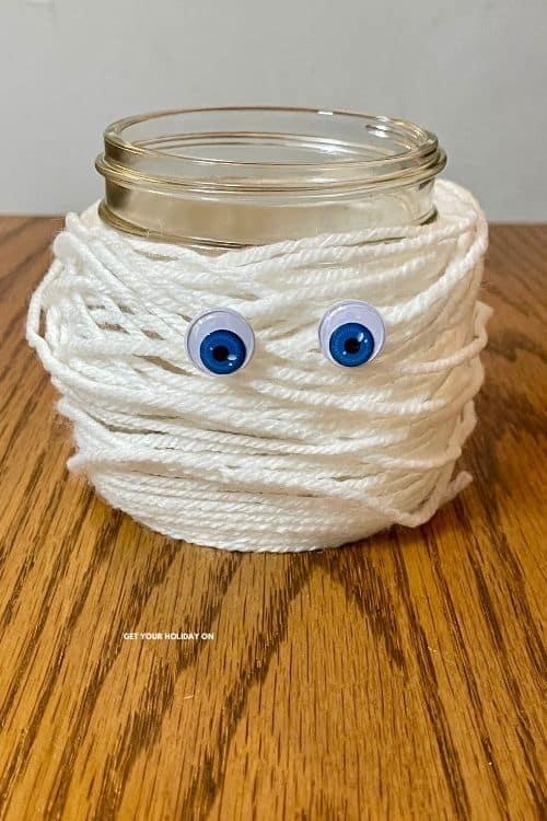 A mummy craft with white yarn wrapped around a mason jar and googly eyes.