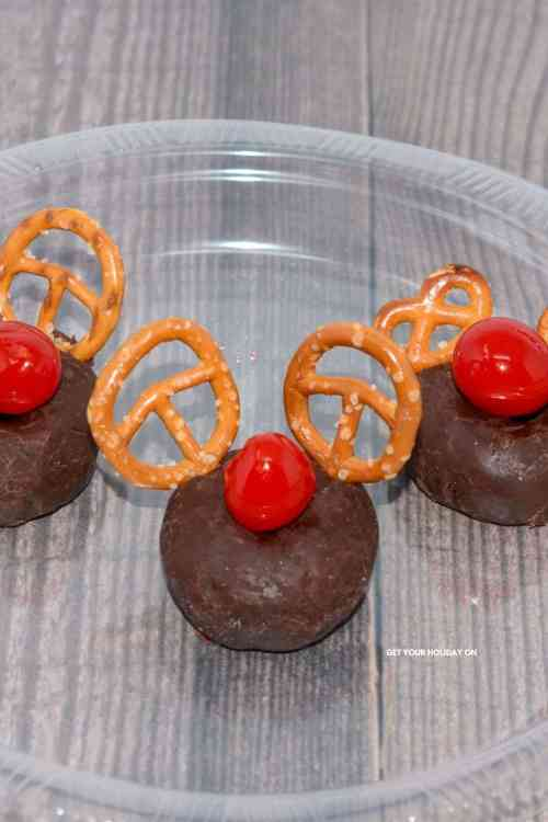 Add the pretzels as shown in picture and then you will need to add the cherry in the middle of the donut to complete the Rudolph donut.