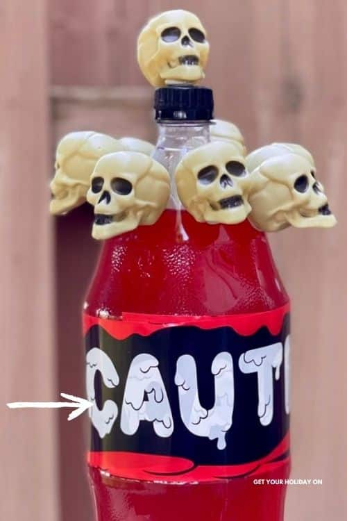 Using caution tape from the dollar store wrap it around the 2-liter bottle a few times to prevent the label from showing through on the dollar tree skull DIY!