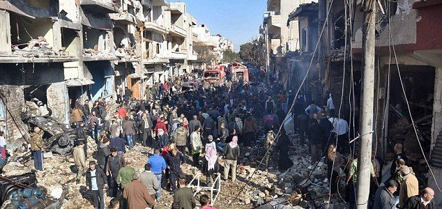 ISIS suicide bomber detonates himself in a crowd as people gather at the scene of a car bomb in Homs