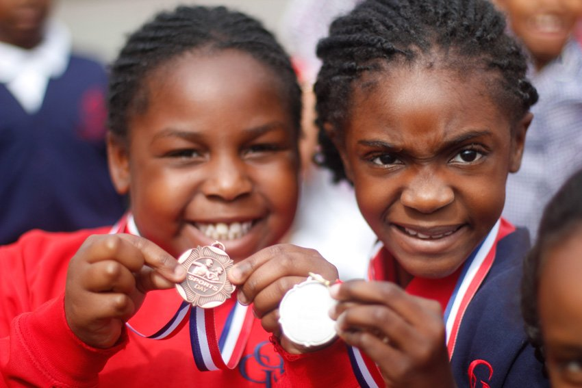 Two girls showing off their Sports Day medals