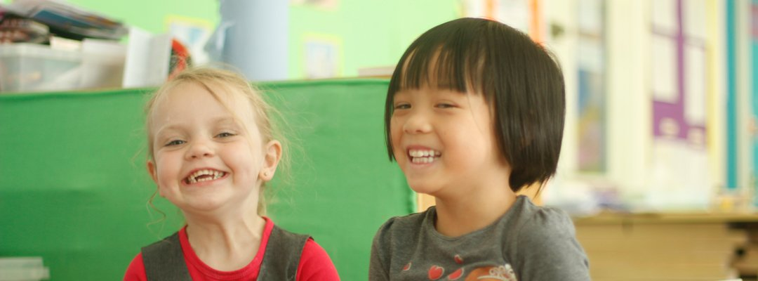 Two young girls laughing during lessons
