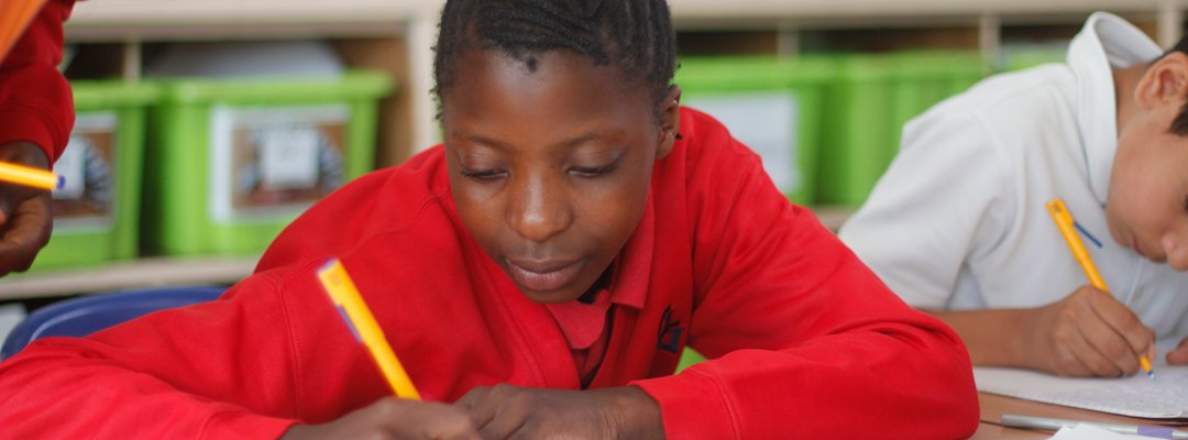Girl writing in her exercise book during a lesson