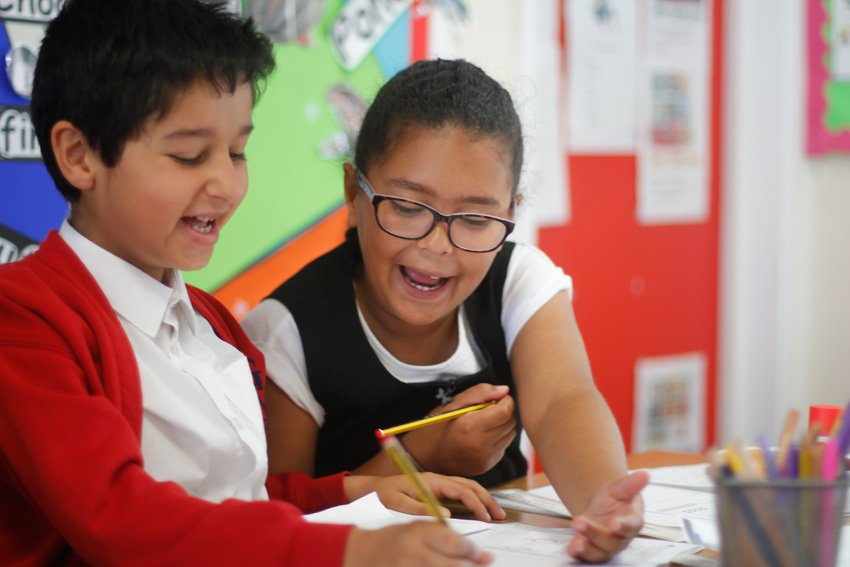 Boy and girl working out a maths problem during their lesson