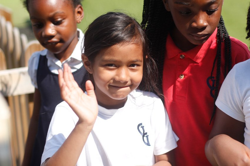 Girl waving during Sports Day
