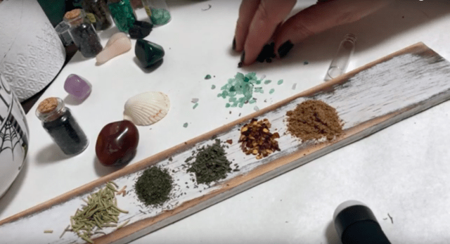 different herbs laid out on a board to put in a spell jar