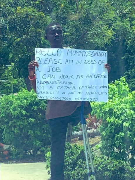 Young man with disability storms the street with placard to search of job