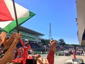 Sebastian Vettel esce festante dalla sua Ferrari dopo la vittoria in Brasile.