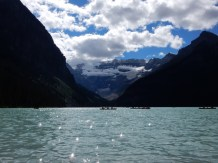 Visitors paddle their canoes on Lake Louise in Alberta.