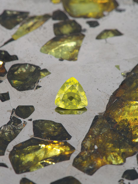 This richly colored 1.12 carat extraterrestrial peridot was extracted from the massive Esquel meteorite, a polished section of which rests behind it. Courtesy of Robert A. Haag; photo by GIA/Robert Weldon.