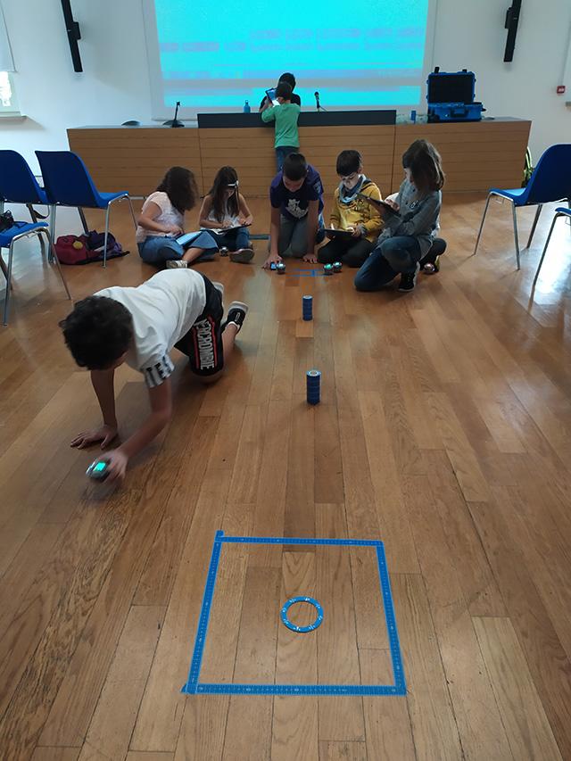 Uno dei gruppi di ragazzi si cimenta con gli Sphero Bolt. Devono programmarli in modo che partendo dal punto A seguano il percorso fino all'arrivo (il cerchio blu)