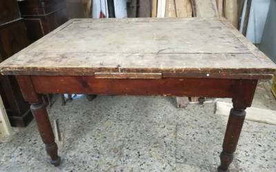 Early 1900s wooden table with pull-out extensions.