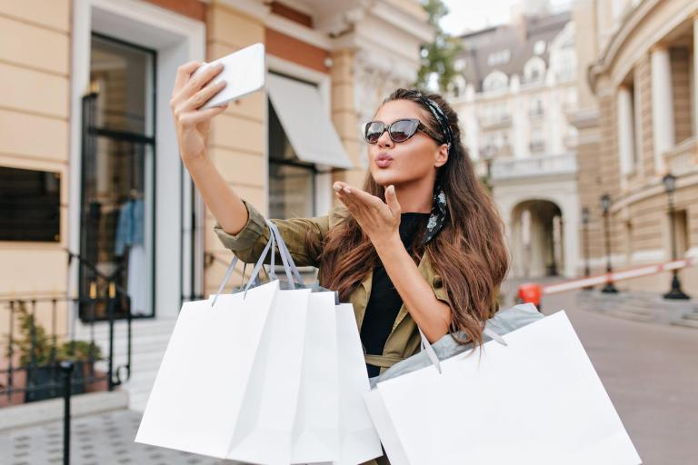 Tanned fashionable woman making selfie with kissing face expression after shopping. Charming shopaholic girl taking picture of herself and sending air kiss, holding purchases.