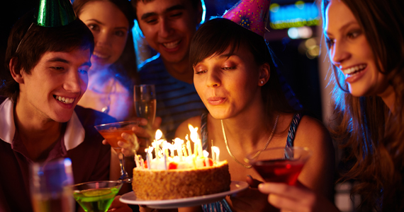 Girl at sixteenth birthday party blowing out birthday candles on cake
