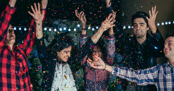young adults throwing confetti at a party