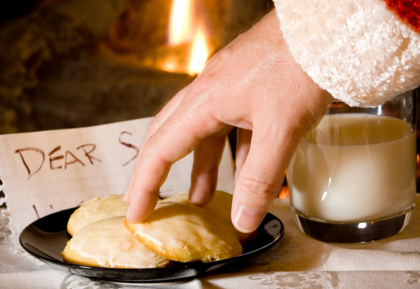 """Santa's hand is reaching for a cookie. """"Dear Santa"""" note and fireplace in the background."""