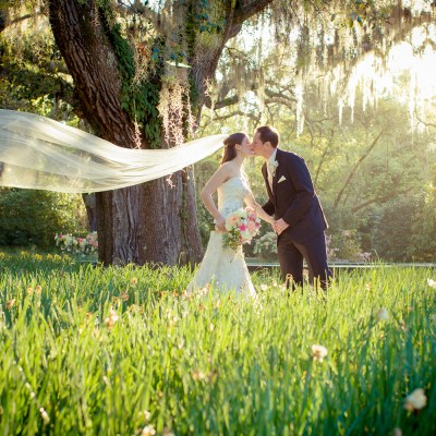 photo of a bride and groom at brookgreen gardens with the veil blowing in the wind by myrtle beach photographer gillian claire