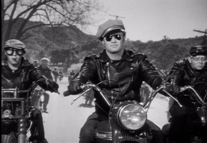Gil Stratton riding alongside Marlon Brando in the Wild One (after teaching him how to ride motorcycles).