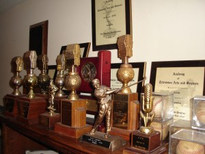 Gil's special award shelf including numerous Golden Mikes. signed baseballs and a couple of Emmies.