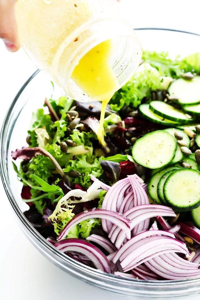 Adding salad dressing to salad bowl
