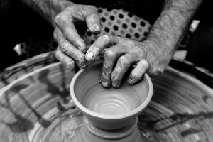 black and white photograph woman's hands on pottery wheel