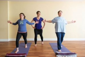yoga instructor stands between two students practicing Warrior I with arms open and bent at the elbow
